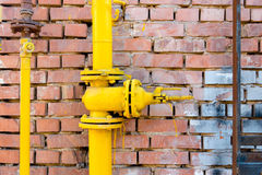 Yellow gas pipe and valve on red brick wall, copyspace Royalty Free Stock Photography