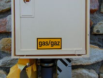 Yellow gas sign on white box of house. Yellow caution gas sign on white box of stone house stock photography