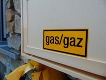 Yellow gas sign on white box of house. Yellow caution gas sign on white box of stone house stock photo