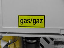 Yellow gas sign on white box of house. Yellow caution gas sign on white box of stone house stock images