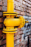 Yellow gas valve over red brick wall Royalty Free Stock Photos