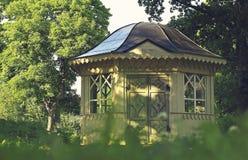Gazebo in Green Park. Yellow gazebo with black roof Stock Photo