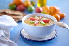 Yellow gazpacho. Gazpacho made with yellow tomatoes. Shallow DOF, focus on garnish tomatoes Stock Image