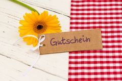Yellow flower with gift tag german word, Gutschein, means voucher or coupon. Yellow gerbera daisy flower with gift card with german word, Gutschein, means Royalty Free Stock Photography