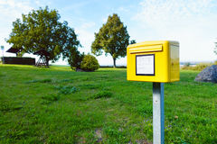 Yellow German postbox one in the green meadow in village Stock Images