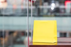 Yellow gift bag in the mall with defocused background. royalty free stock photo