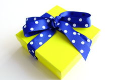 Yellow gift box and blue dotted ribbon isolated. Over white Stock Photo