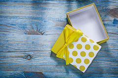 Yellow gift box with bow on wooden board holidays concept Stock Images