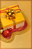 Yellow gift box with christmas baubles and beads Royalty Free Stock Images