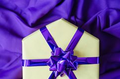 Yellow gift box with a purple bow. stock image