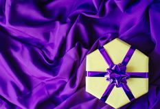 Yellow gift box with a purple bow. stock photography