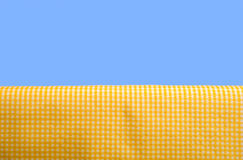 Yellow Gingham Tablecloth. A yellow gingham or checked tablecloth background on a blue sky background Royalty Free Stock Image