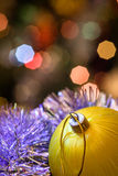Yellow glass ball lie in Christmas tinsel. Royalty Free Stock Image