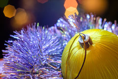 Yellow glass ball lie in Christmas tinsel. Stock Photos