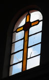 Yellow glass crux in a church. A glass window shows a crux made of glass in yellow color, some crystals are broken in a church in mexico Royalty Free Stock Photos