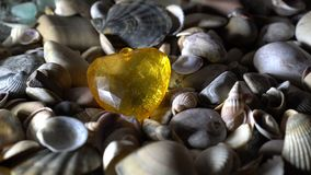 The yellow glass heart lies on the sea pebbles. Close-up, high detail. Rotation. 4K. 25 fps stock video