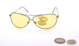 Yellow glasses and coins Stock Photos