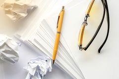 Yellow glasses and a gold washed-out old fountain pen of the writer, white paper and crumpled paper. White background Royalty Free Stock Photos