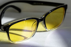 Yellow glasses on the table refracts light. Glasses with yellow lenses protection monitors, glasses and reflected light from them Royalty Free Stock Photography