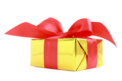 Yellow glossy gift wrapped present with red satin bow Stock Images