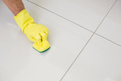 Yellow gloved hand with sponge cleaning the floor Stock Photography