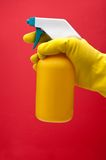 Yellow gloved with a spray bottle on red Royalty Free Stock Photo