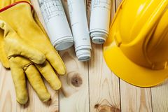 Yellow gloves blueprints and construction helmet on wood royalty free stock images