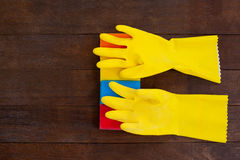 Yellow gloves with scouring pad on a wooden floor Royalty Free Stock Photography