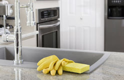 Yellow gloves and sponge in kitchen. Yellow gloves and sponge on sink in modern kitchen - housekeeping stock photography
