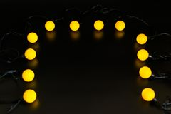 Yellow glowing garland neatly straight-lined balls on a black background with light reflection.  stock images