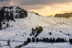 Yellow glowing sky above the snow covered hill. Lovely sunset in mountains. yellow glowing sky above the snow covered hill stock photo