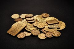 Yellow gold bars and coins isolated on black background.  Stock Photography
