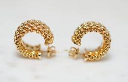 Yellow gold hoop earrings stock photography