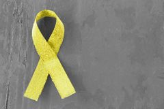 Yellow, gold ribbon on black and white wooden background, close-up, copy space, medical concept, Suicide Prevention Day stock image