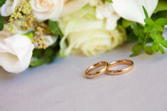 gold wedding rings. Yellow  Gold wedding ring on table with flower bouquet Royalty Free Stock Photography