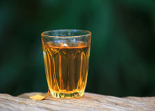 Yellow golden alcoholic drink in a brandy glass, on a wood table Stock Photo
