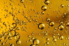 Water and oil bubbles. Yellow and golden bubbles oil in water, abstract background royalty free stock images