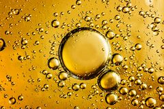 Water and oil bubbles. Yellow and golden bubbles oil in water, abstract background stock photos