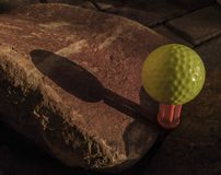 Yellow Golf Ball On Brush Tee Placed Between Rocks stock images
