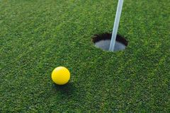 Yellow golf ball nearby hole with pin flag, green grass background royalty free stock images