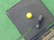 Yellow Golf Ball with Putter. Yellow minature golf ball on green, ready to tee off Stock Photos