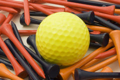 Yellow golf ball and tees. Yellow golf ball and orange and blue tees Royalty Free Stock Images