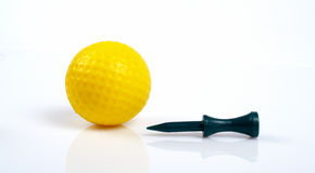 Yellow golfball and green tee with reflecting. On white background Royalty Free Stock Photography