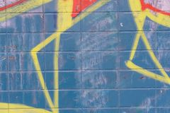 Yellow graffiti details on blue tiles wall. Abstract background. Exterior wall stock image