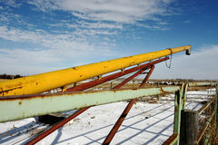 Yellow Grain Auger. Yellow auger sitting along fence on farm in midwest in winter Royalty Free Stock Images