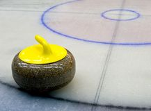 Yellow granite stone for curling game on the ice Stock Images