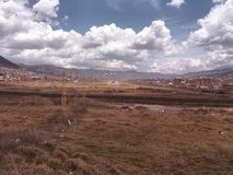 Yellow grass in airport and plane. Yellow meadow in airport and plane landing, blue sky with black clouds in the background, location in the city of Cusco, Peru royalty free stock photos