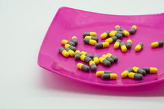 Yellow and gray capsule medicines on pink. Plastic plate Royalty Free Stock Images
