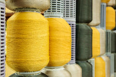 Yellow and gray silk thread in spool. Yellow and gray silk thread roll in silk spool Stock Photo