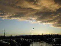 Yellow gray storm clouds. Cumulonimbus dramatic sky wave formation over the city. Weather after the thunderstorm, light. Blue sky and sunset sun shining glow royalty free stock photography